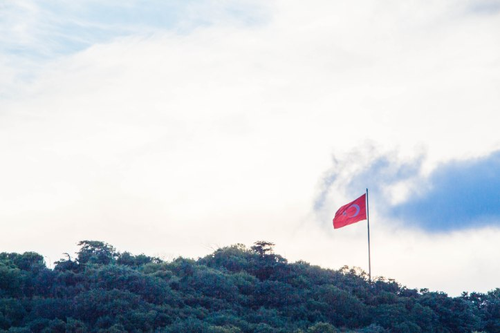 The Turkish flag fluttering atop a hill, with clear skies forming a natural background.